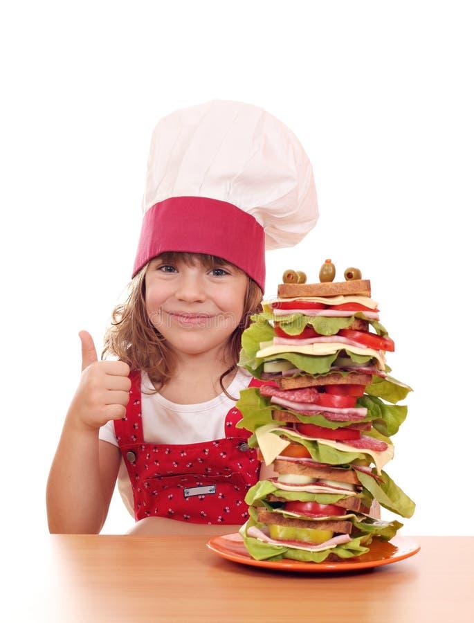 Mała dziewczynka kucharz z kanapką up i kciukiem zdjęcie stock
