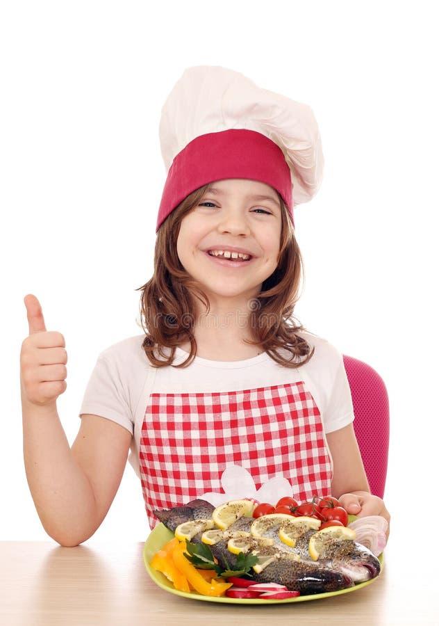 Download Mała Dziewczynka Kucharz Z Pstrąg Up I Kciukiem Zdjęcie Stock - Obraz złożonej z femaleness, rozochocony: 53780540