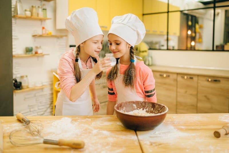 Mała dziewczynka kucharzi obwąchuje wanilia proszek w nakrętkach zdjęcie stock