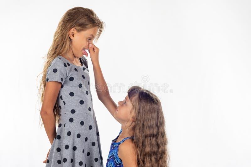 Mała dziewczynka ledwo dosięgał dla nosa wysoka dziewczyna zdjęcie stock