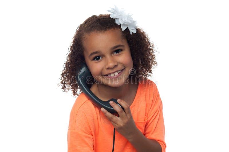 Mała dziewczynka mówi nad telefonem zdjęcia stock