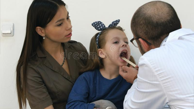 Mała dziewczynka ma gardło egzamin męską lekarką zdjęcie royalty free