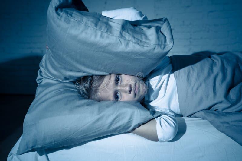 Mała dziewczynka ma kłopotu dosypianie przy nocy mienia poduszką zakrywa jej głowę niepokojących ucho i fotografia stock