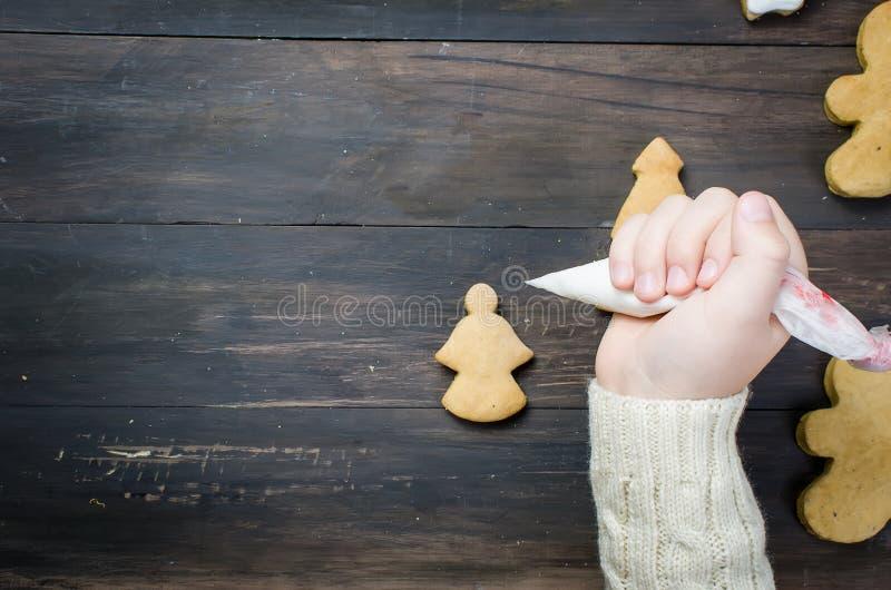 Mała dziewczynka maluje domowej roboty piernikowego mężczyzna bożych narodzeń ciastek znaleziska wizerunki patrzeją więcej mój po zdjęcie stock