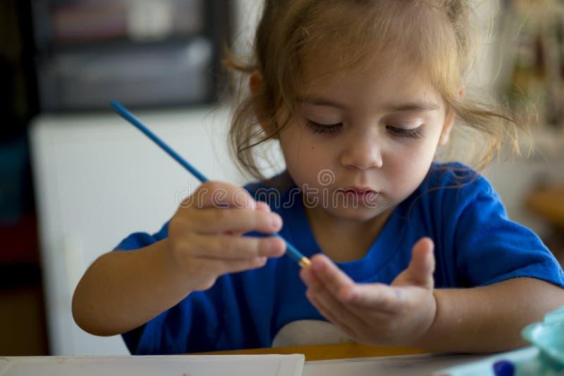 Mała dziewczynka maluje jej rękę obraz stock
