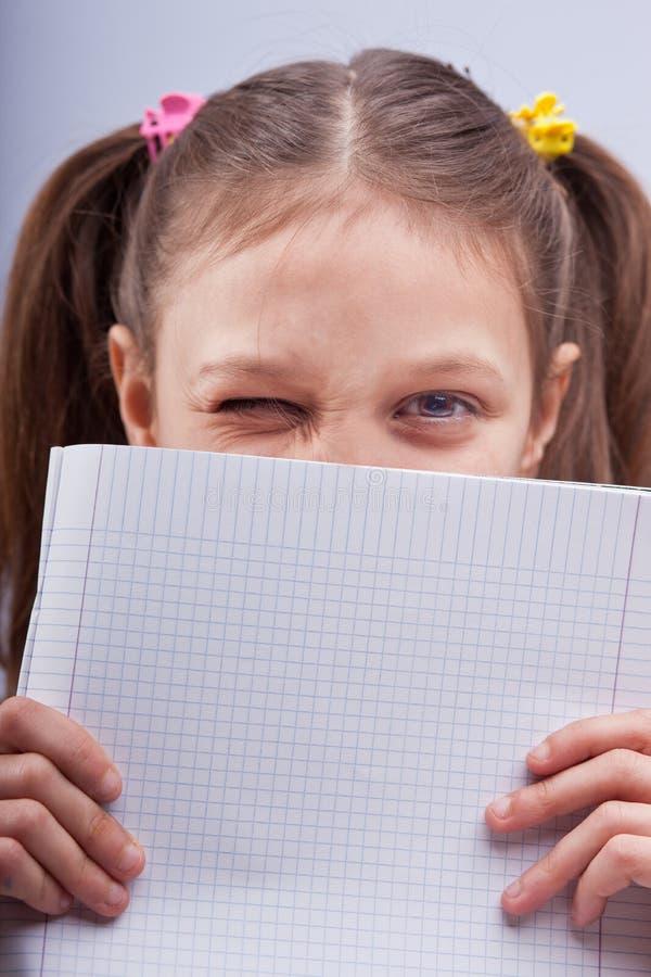 Mała dziewczynka mruga za ciosową ćwiczenie książką obrazy stock