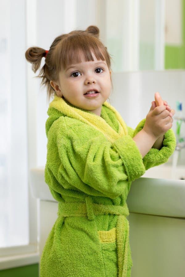 Mała dziewczynka myje jej ręki w łazience fotografia stock