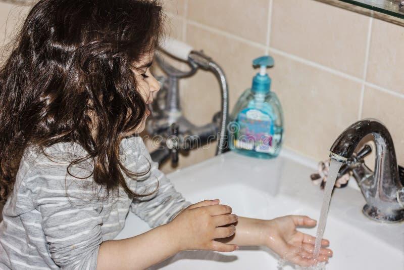 Ma?a dziewczynka myje jej r?ki w ?azience pod wod? bie??c? fotografia royalty free