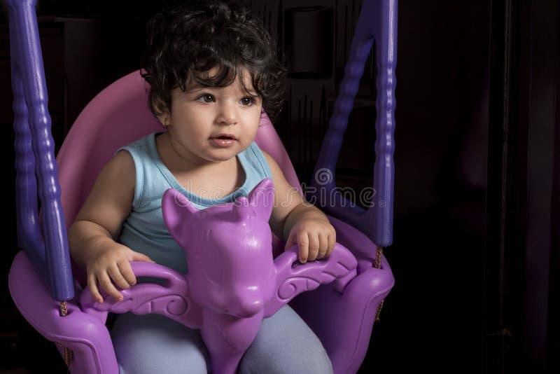 Mała dziewczynka na jednorożec huśtawce, wyposażającej w domu obraz stock