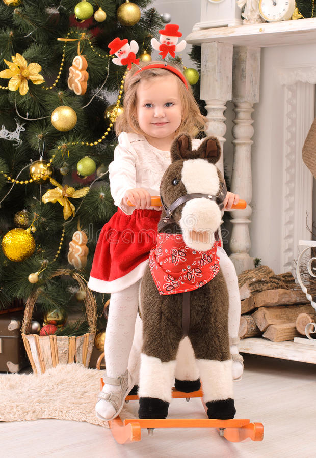 Mała dziewczynka na zabawkarskim koniu w bożych narodzeniach wewnętrznych zdjęcie royalty free