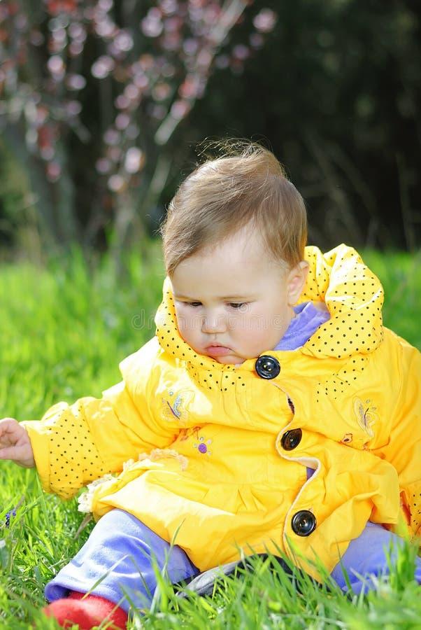 Mała dziewczynka na zielonej łące w jaskrawej żółtej kurtce zdjęcia stock