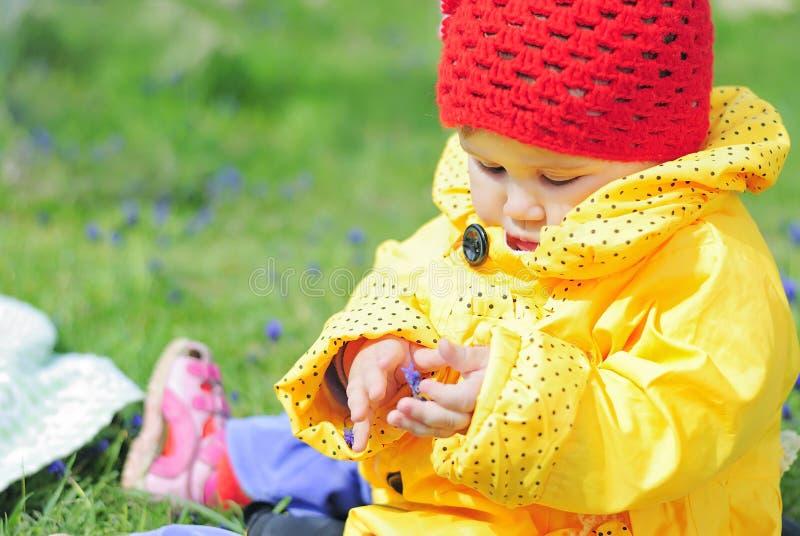 Mała dziewczynka na zielonej łące w jaskrawej żółtej kurtce obraz royalty free