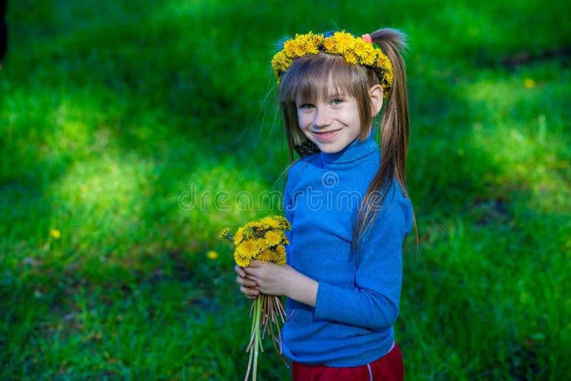 Mała dziewczynka na zielonej trawie w wianku kwiaty w wiośnie zdjęcie royalty free