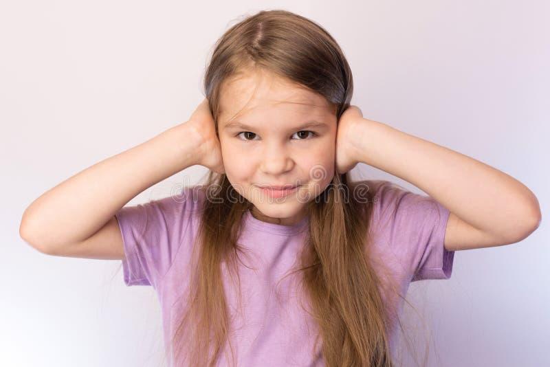 Mała dziewczynka nakrywkowi ucho, nieznacznie ono uśmiecha się na lekkim tle obrazy royalty free