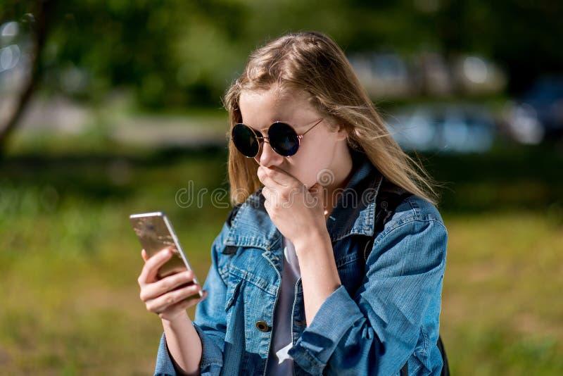 mała dziewczynka nastolatek W lecie w parku W jej rękach trzyma smartphone w drelichowej kurtce i okularach przeciwsłonecznych, _ fotografia royalty free
