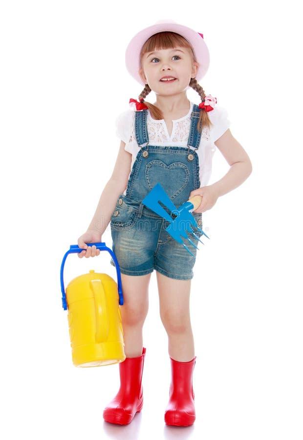 Mała dziewczynka nawadnia ogród zdjęcie royalty free