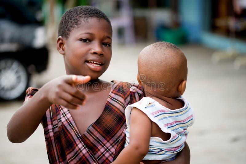 Mała dziewczynka niesie jej młodszego brata zdjęcie royalty free