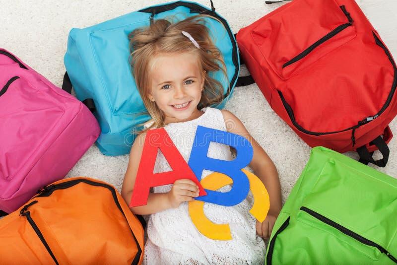 Mała dziewczynka niespokojna iść szkoła - kłamający na podłoga wśród c obrazy stock