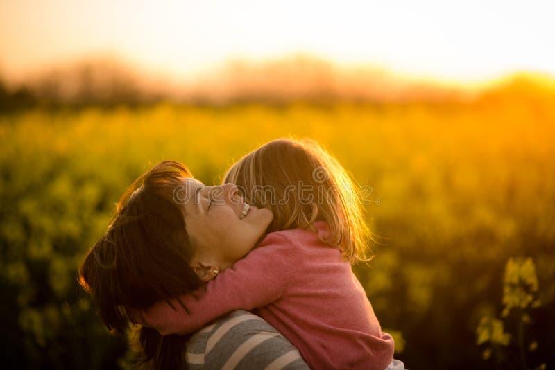 Mała dziewczynka obejmuje jej mamy w rapeseed polu obraz royalty free