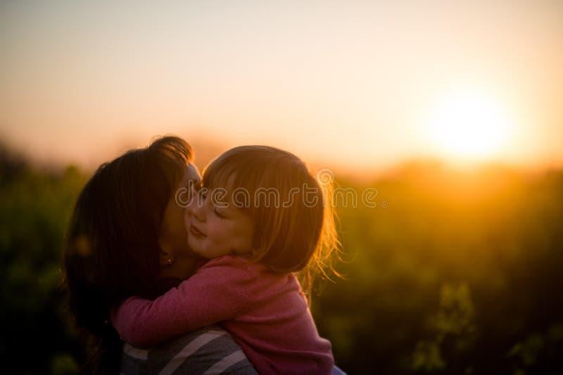 Mała dziewczynka obejmuje jej matki outdoors, zmierzchu tło obraz royalty free