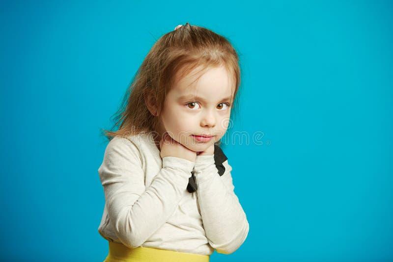Mała dziewczynka opierał jej pięści podbródek, stojaki na błękicie zdjęcie stock