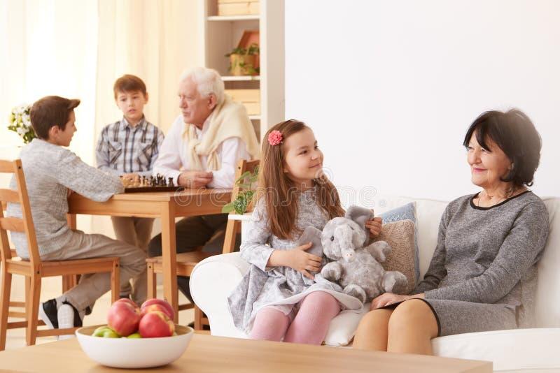 Mała dziewczynka opowiada z babcią w żywym pokoju obrazy royalty free