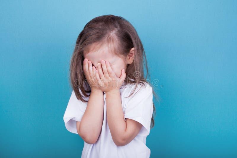 Mała dziewczynka płacz zakrywa jej twarz z ona ręki obraz stock