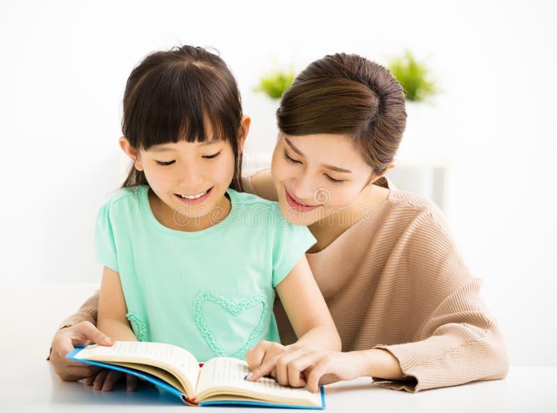 Mała dziewczynka patrzeje książkę z jej matką zdjęcie royalty free