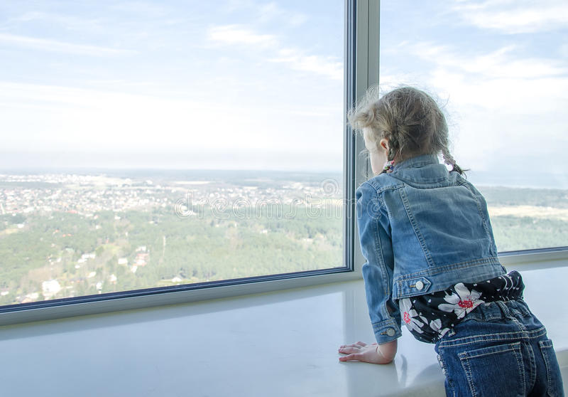Mała dziewczynka patrzeje przez okno zdjęcie royalty free