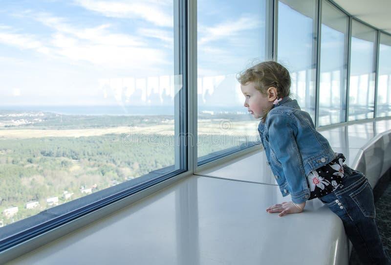 Mała dziewczynka patrzeje przez okno zdjęcia royalty free