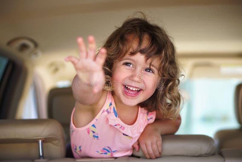 Mała dziewczynka patrzeje szczęśliwą w samochodzie zdjęcie stock