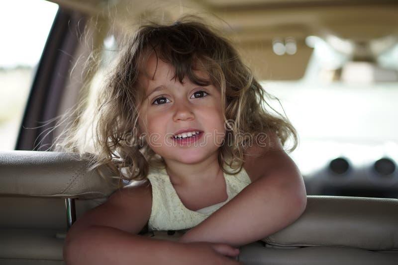 Mała dziewczynka patrzeje szczęśliwą w samochodzie fotografia stock