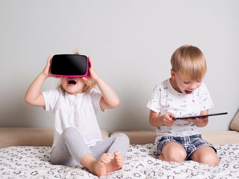 Mała dziewczynka patrzeje w rzeczywistości wirtualnej chłopiec z touc i szkłach zdjęcie stock