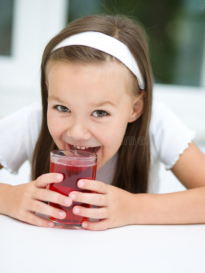 Mała dziewczynka pije czereśniowego sok zdjęcie royalty free