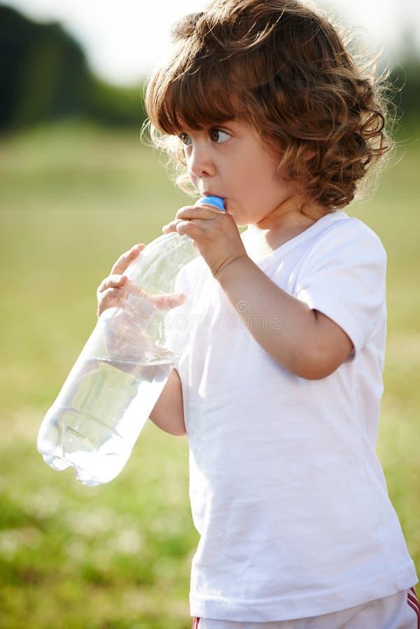 Mała dziewczynka pije czystą wodę od butelki fotografia stock