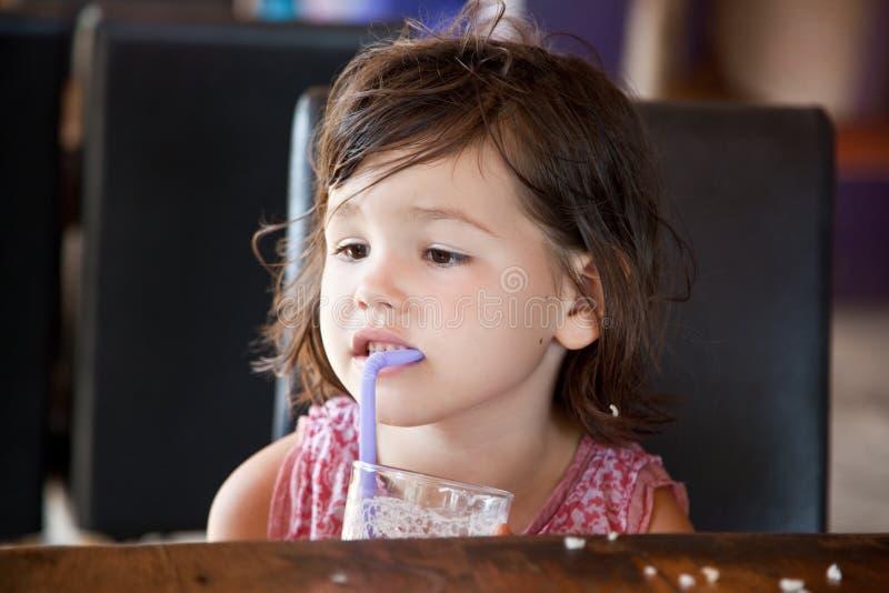 Mała dziewczynka pije dojnego koktajl zdjęcia stock