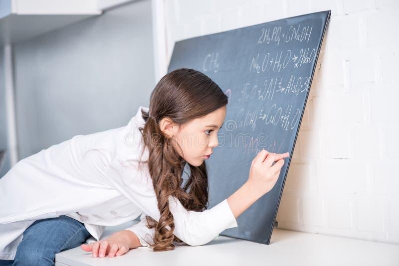 Mała dziewczynka pisze chemicznej formule zdjęcia stock