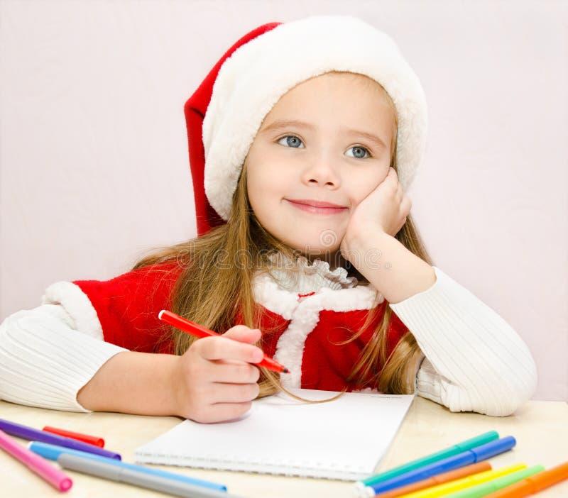 Mała dziewczynka pisze liście Santa obraz stock