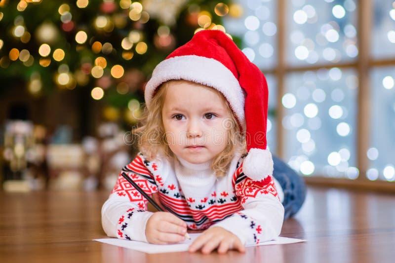 Mała dziewczynka pisze liście Santa Cla w czerwonym Bożenarodzeniowym kapeluszu zdjęcie royalty free