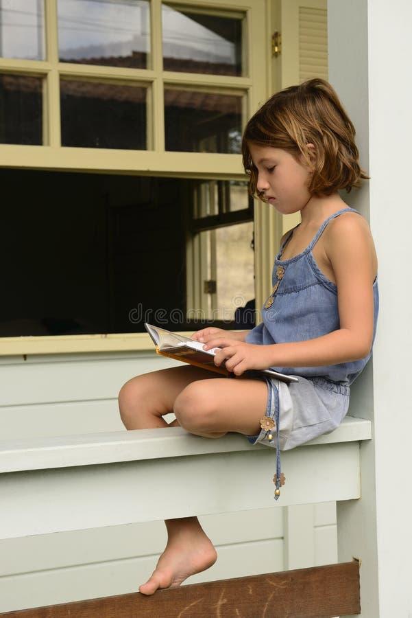 Mała dziewczynka pod światłem dziennym czyta książkę bajki, w domu zdjęcie royalty free