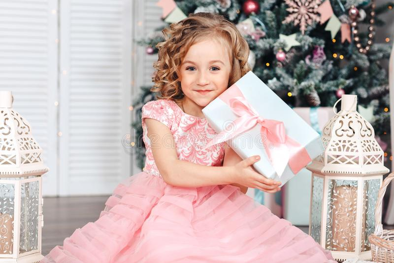 Mała dziewczynka pod choinki odpakowania teraźniejszość zdjęcie royalty free