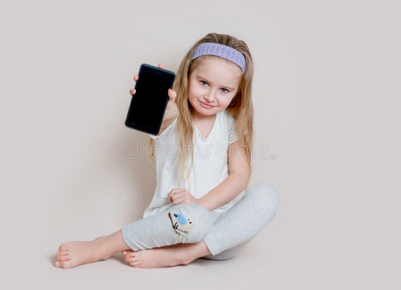 Mała dziewczynka pokazuje pustego ekran telefon komórkowy obrazy royalty free
