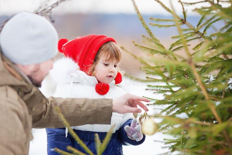 Mała dziewczynka pomaga jej ojca dekoruje boże narodzenia trzy plenerowych zdjęcia royalty free