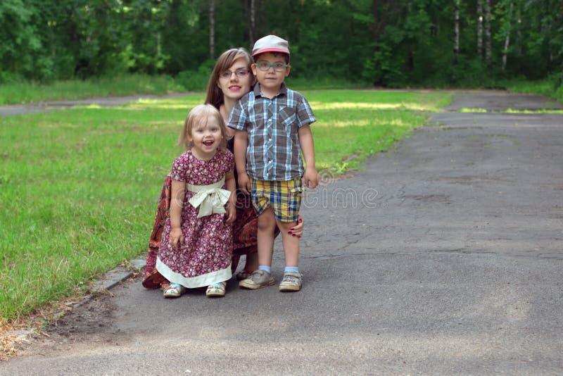 Mała dziewczynka, potomstwa matki i chłopiec poza w parku przy pogodnym d, obraz royalty free