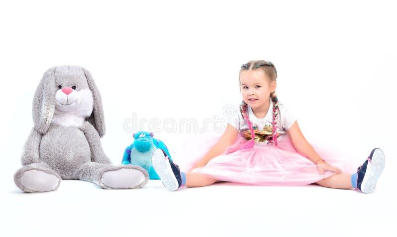 Mała dziewczynka pozuje wraz z dużymi zabawkami zdjęcie royalty free