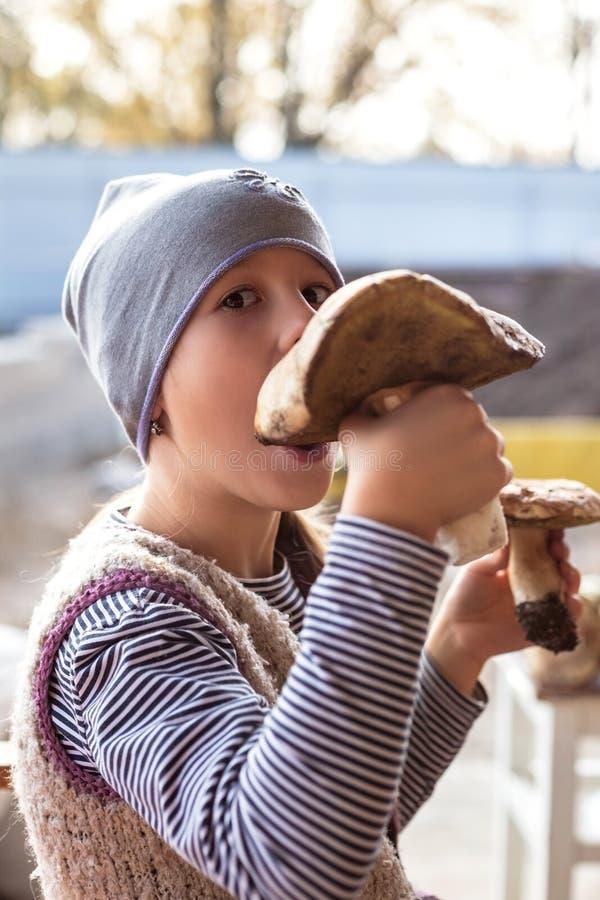 Mała dziewczynka próbuje jeść dużej surowej jadalnej pieczarki zdjęcia stock