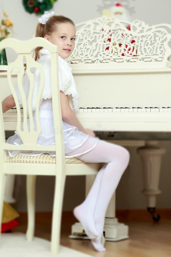 Mała dziewczynka przy białym Uroczystym pianinem zdjęcie stock