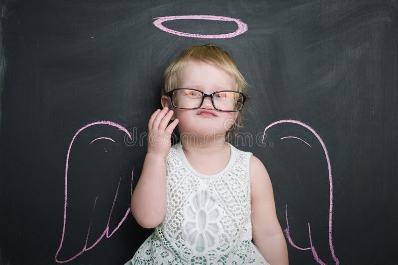 Mała dziewczynka przy blackboard z skrzydłami i halo fotografia royalty free