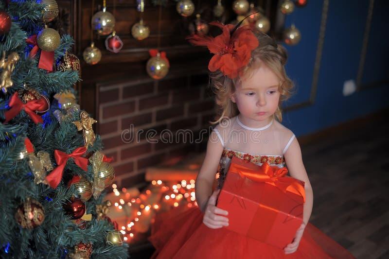 mała dziewczynka przy choinką w czerwonej eleganckiej sukni z pudełkiem z prezentami w jej rękach zdjęcie stock