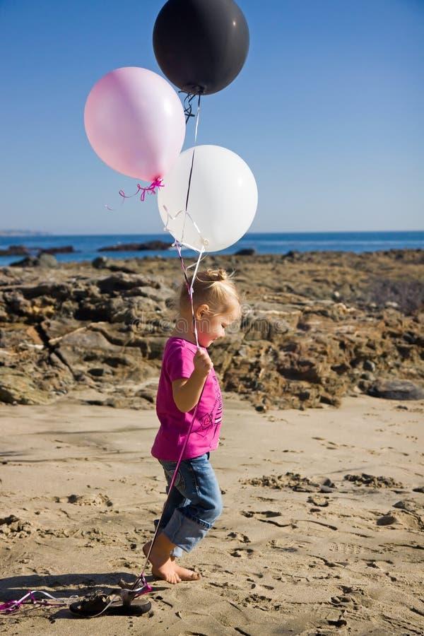 Mała Dziewczynka przy Plażowymi mienie balonami zdjęcie stock